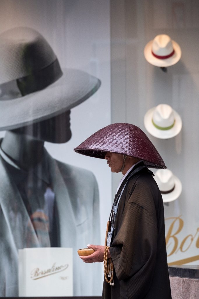 A monk wearing an iconic Japanese hat, or Kasa, standing in front of a modern hat shop. Photographed by Lukasz Palka.