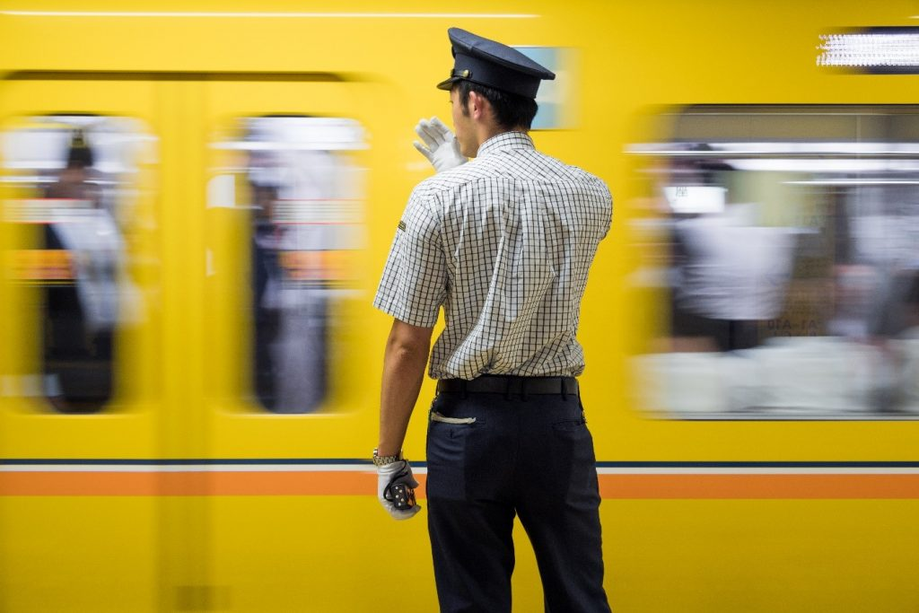 A yellow train rushes past an isolated conductor. Photographed by Lukasz Palka.
