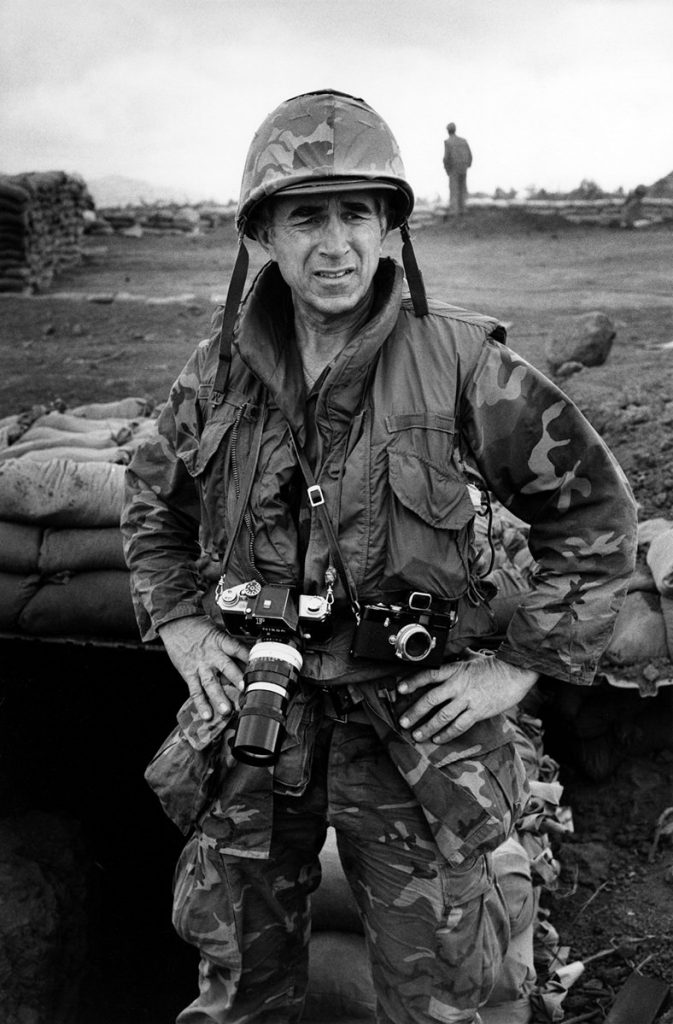 Mr. Duncan covering the Vietnam War in 1968. He carries a Nikon F camera attached with a NIKKOR 200mm lens.