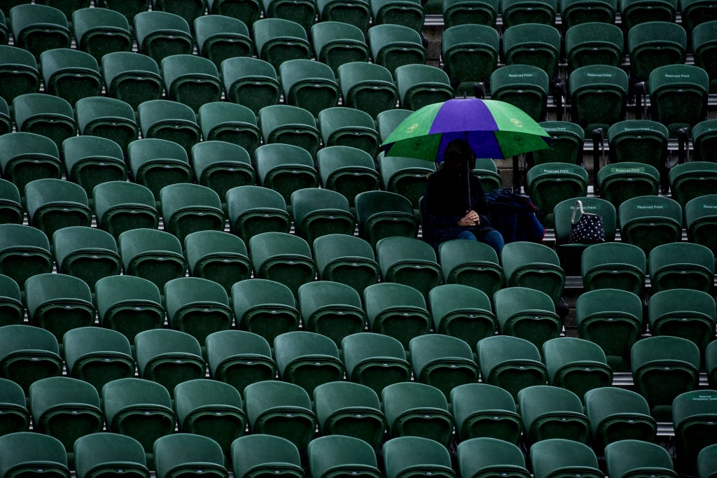 Wimbledon Weather: a woman sits in the stands of No.2 Court when play is being suspended due to rain at The Wimbledon Championships on June 29, 2016 in London, England. Nikon D5 + NIKKOR 70-200mm f/2.8 @ f/4 | 200 mm | 1/800s | ISO 1600 © AELTC/Joel Marklund