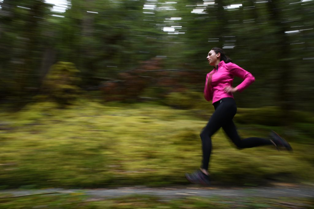 Woman in pink jumper running through green forest, capturing by Scott Woodward using a Nikon D7500
