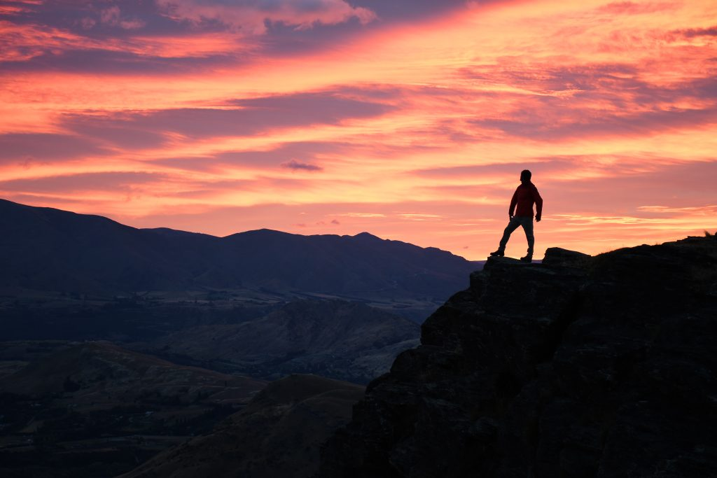 Man silhouetted against red evening sky on top of rock, captured by Scott Woodward using a Nikon D7500