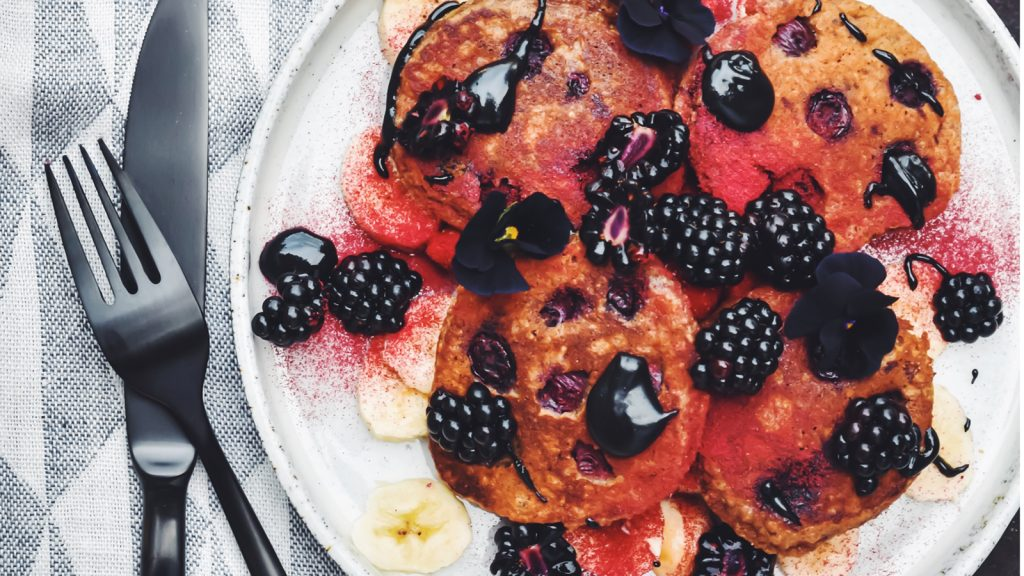 Pancakes with black tahini drizzles and cranberry dust