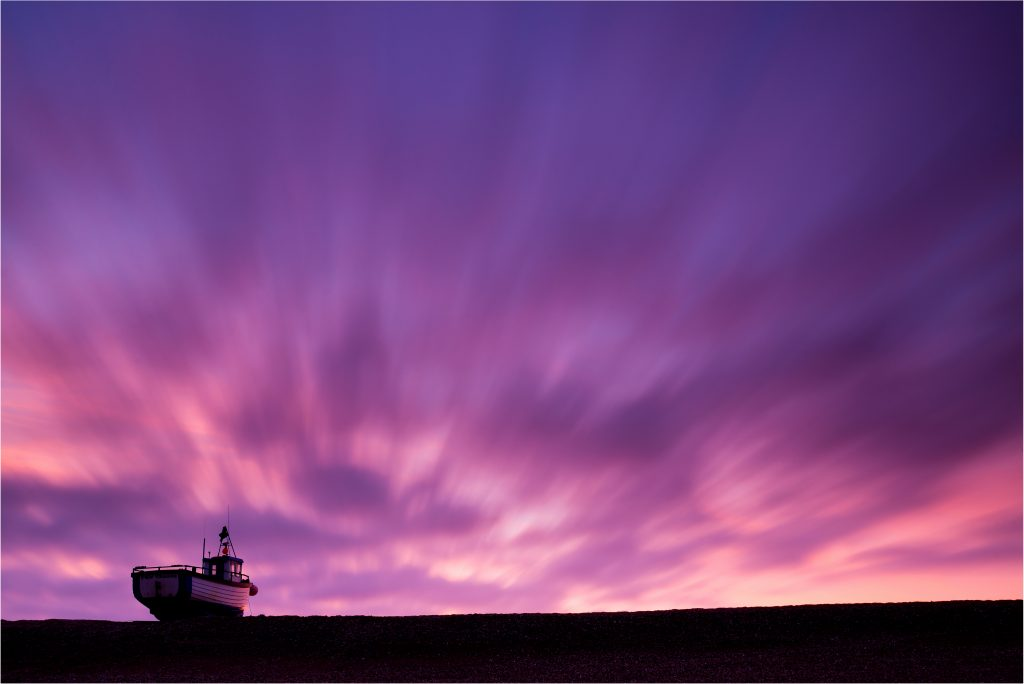 Fishing boat on shingle bank at sunset by Robert Canis purple skies