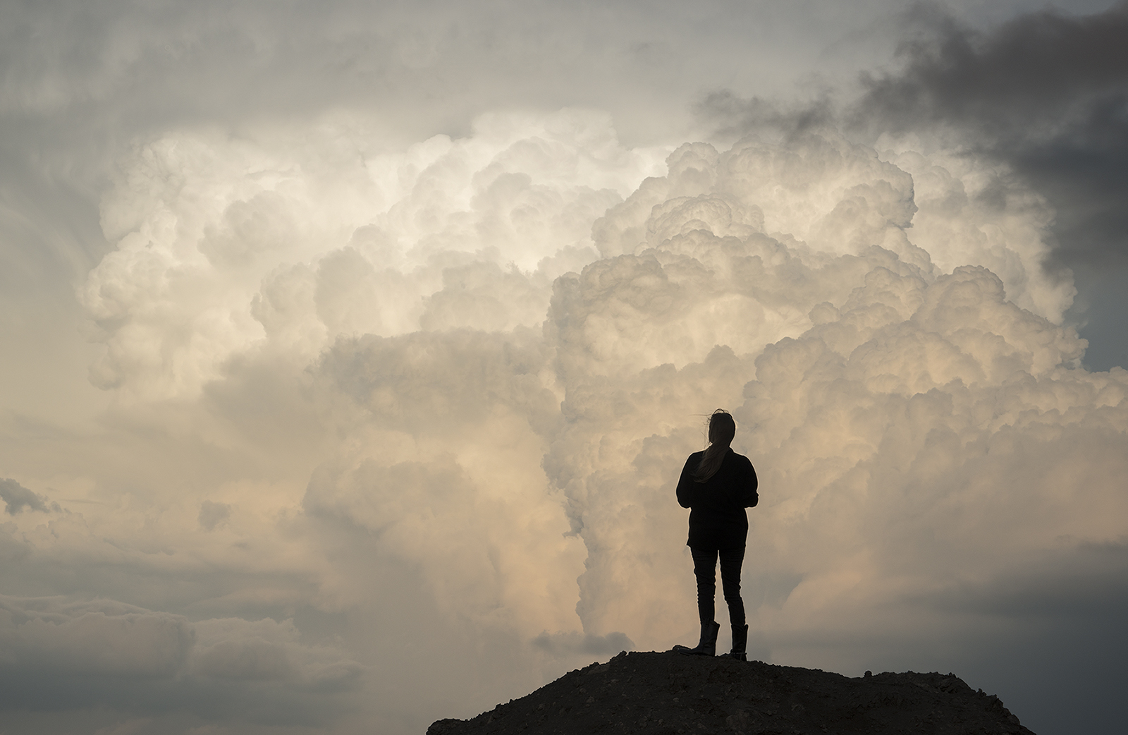 A woman in silhouette watches a picturesque storm from atop a hill.