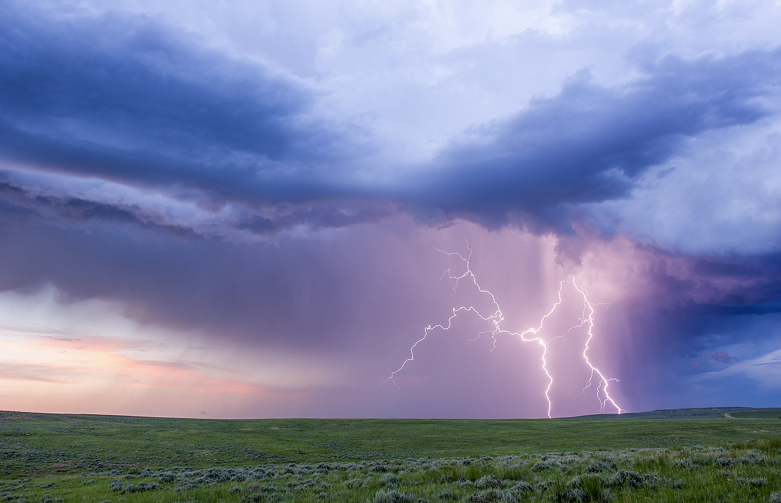 Cloud-to-ground lightning bolts strike a field in eastern Wyoming.