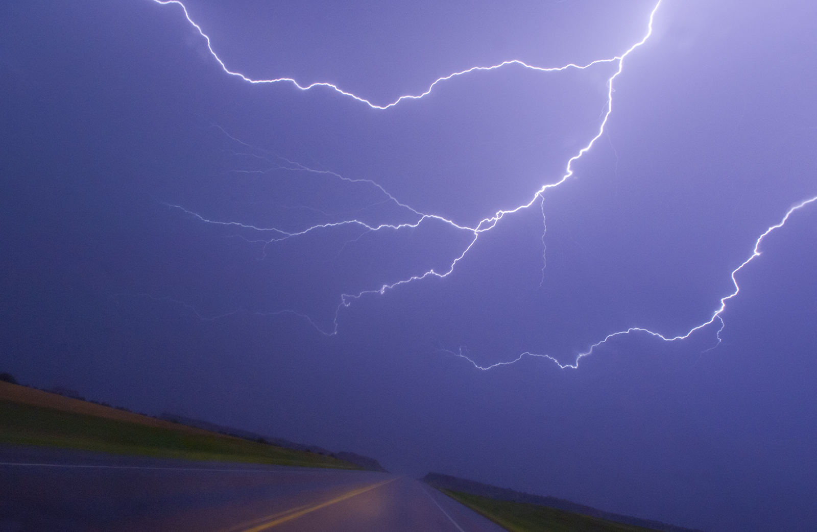 """Lightning Over Road, Oklahoma, 2005"" -- Lightning wriggles over a highway in north central Oklahoma on June 16, 2005."